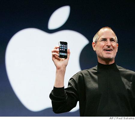 Steve Jobs con l'iPhone in piedi davanti al logo Apple